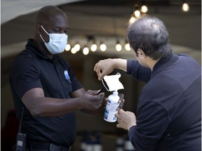 A security guard helps a man disinfect his hands and change masks before he enters the COVID-19 vaccination centre at the Bill Durnan Arena in Montreal on July 21, 2021.