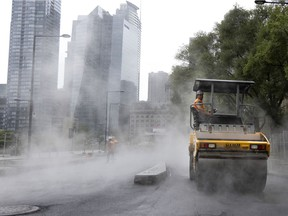 Steam rises off the hot asphalt as rain falls on a crew paving Peel Street in the Griffintown district of Montreal on August 9, 2021.