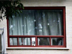 Bullet holes are visible from the street after a St-Léonard triplex was targeted with gunfire Friday morning. Police are investigating the scene.