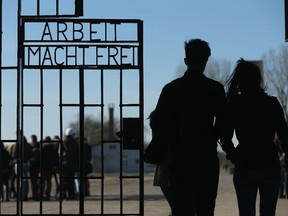 """Visitors walk through the infamous """"Arbeit Macht Frei"""" (""""Work Makes Free"""") inscription at the original entrance gate to the former Sachsenhausen concentration camp near Berlin on March 18, 2015 in Oranienburg, Germany."""