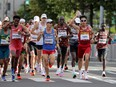 Runners sprinkle water at the refreshment point while competing in the men's marathon final during the Tokyo 2020 Olympic Games in Sapporo on August 8, 2021. Researchers' observation that competitive running is an injury risk could be related to a number of factors, including high volume training and failure to let the body fully recover between hard training runs, Jill Barker writes.