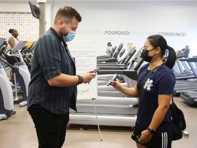 A patron has their vaccine passport scanned at an  Econofitness gym in Laval, Quebec, Canada August 17, 2021.