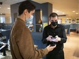 Thomas Resendes, right, scans a QR code from client Jasmin Lauriere, at a Cora restaurant in downtown Montreal on Sept. 1, the first day that restaurants had to ask for the vaccine passport to clients.