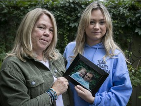 Kimmy Chedel, left, with her daughter Zoë Doyle holds a picture of her late husband Frank Doyle who died on 9/11. Zoë is the baby in the picture.