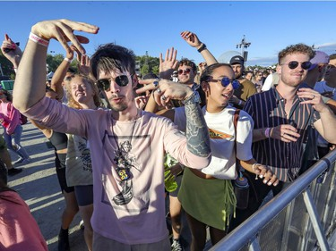 Anthony Pageau, left, Meriem Benzakour and Jasmin Petit dance to the beats of DJ Spencer Brown at the Île Soniq Redux electronic music festival at Parc Jean-Drapeau in Montreal on Friday, Sept. 24, 2021.