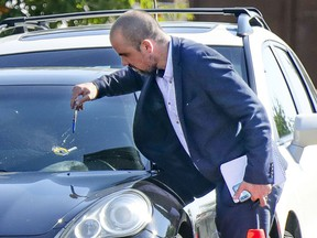 A Montreal police investigator examines a bullet hole in a car at the scene of a shooting in Montreal's Rivière-des-Prairies district on Tuesday Aug. 3, 2021.