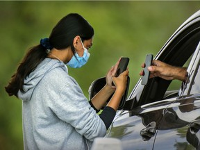 A nurse scans a client's information at the commercial drive-thru COVID-19 testing tent at Fairview Pointe Claire mall west of Montreal Sunday September 5, 2021.