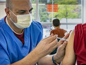 Vaccinator Saled Fahd administers a dose of vaccine to a man at the COVID-19 vaccination site on Park Ave. in Montreal Friday September 10, 2021. (John Mahoney / MONTREAL GAZETTE) ORG XMIT: 66663 - 7422
