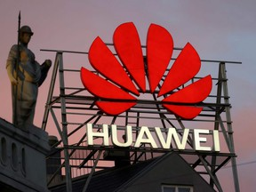 The logo of Chinese telecommunications giant Huawei Technologies is pictured next to a statue on top of a building in Copenhagen, June 23, 2021.