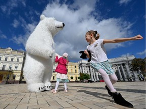 Children play with an environmental protester wearing a costume of a polar bear during a climate march in the Ukrainian capital, Kiev, on Sunday, Sept. 26, 2021.