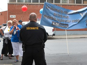 """A security guard stands watch as locked out Journal de Montréal employees protest in 2010. A court ruling at the time found that Quebec's anti-scab law applied only to work performed in the """"establishments"""" of the employer, opening the door to work performed off-site by strikebreakers."""