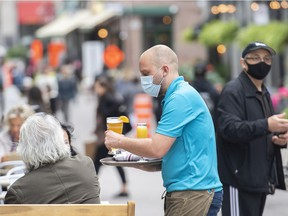 A server wears a face mask as he brings drinks to customers on an outdoor terrasse at a restaurant in Montreal on Oct. 3, 2021.