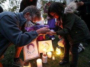 People gather for a candlelight vigil on the first anniversary of the death of Joyce Echaquan, an Indigenous woman who died while subjected to insults at a Quebec hospital, in Montreal on Sept. 28, 2021.