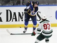Blues' Mike Hoffman flips the puck past the Wild's Kirill Kaprizov last season. Hoffman signed a three-year, US$13.5-million contract with the Canadiens this off-season.