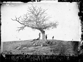Soldiers stand next to a lone grave after the Battle of Antietam near Sharpsburg, Md., in 1862, the bloodiest one-day battle in American history