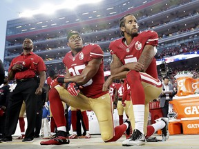 In this Sept. 12, 2016 file photo, San Francisco 49ers safety Eric Reid (left) and quarterback Colin Kaepernick kneel during the national anthem before a game against the Los Angeles Rams.