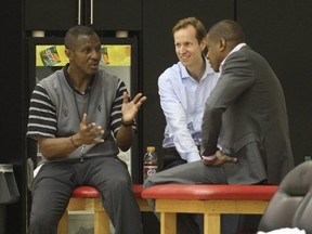 In this 2013 file photo, Toronto Raptors head coach Dwane Casey, then-general manager Jeff Weltman and president Masai Ujiri talk at a practice.