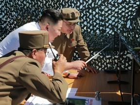 This picture released by North Korea's official Korean Central News Agency shows  leader Kim Jong-Un inspecting the ground jet test of a new type high-power engine of a carrier rocket.