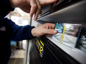 A corner store owner in St. Thomas, Ontario, Canada holds a package of cigarettes on March 12, 2012.