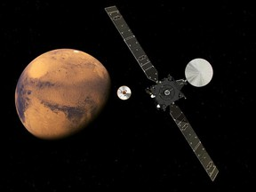 In this artist impression provided by the European Space Agency, ESA, the  ExoMars Trace Gas Orbiter, TGO, right, and its entry, descent and landing demonstrator module, Schiaparelli, center, approaching Mars. The separation was scheduled to occur on Sunday Oct. 16, about seven months after launch. One of the NASA scientists involed in Mars research and swept up in raids last year in Turkey remains in prison.