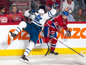 Toronto's Matt Martin (left) slams into the boards as he tries to check Montreal's Sven Andrighetto on Oct. 6.