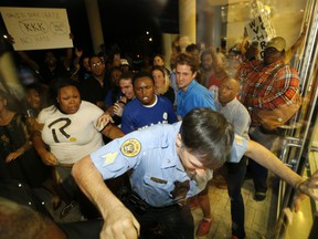 A police officer pushes his way outside to keep protesters at bay, before a debate for Louisiana candidates for the U.S. Senate, at Dillard University in New Orleans, Wednesday, Nov. 2, 2016.