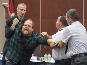 Security guards try to restrain a demonstrator from interrupting the National Energy Board public hearing into the proposed Energy East pipeline project on Aug. 29, 2016 in Montreal.