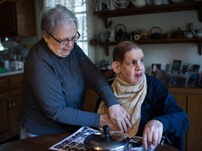 Barbara Altman helps her son Andy get ready for lunch during a weekend stay at his parents' home in Rockville, Md.