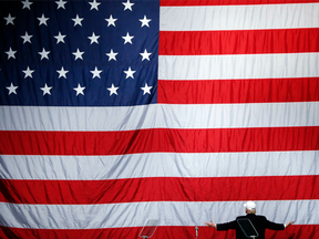 Donald Trump turns to a large U.S. flag during a campaign rally in Sterling Heights, Mich., on Sunday, Nov. 6, 2016.