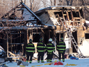 Firefighters and Ontario Fire Marshall officials at the scene of a fatal house fire on Oneida Nation of the Thames, southwest of London, Ont., Dec. 15, 2016.