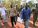 In this photo taken Friday, Jan. 16, 2015 and released by the Uganda People's Defence Force (UPDF), a man said by the UPDF to be the wanted Lord's Resistance Army (LRA) commander Dominic Ongwen, center-right, is handed over by the UPDF to the African Union Regional Task Force who later handed him over to Central African Republic authorities, in the Central African Republic.