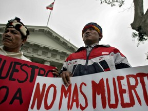 """Members of Peru's Achuar ethnic group protest  against oil companies before the Congress in Lima, 19 June 2007. The banner on the right reads """"No more deaths""""."""