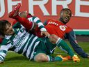In this March 28, 2012 file photo, Toronto FC defender Ashtone Morgan (right) lies tangled up on the pitch with an opponent from Mexico's Santos Laguna during a CONCACAF Champions League semi-final in Toronto.
