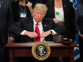 U.S. President Donald Trump takes the cap off a pen to sign an executive order to start the Mexico border wall project at the Department of Homeland Security facility in Washington, DC, on January 25, 2017.