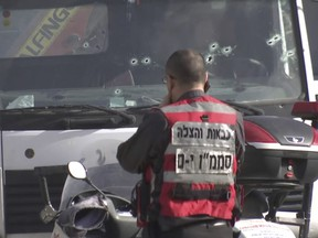 This frame grab from video, shows an Israeli emergency services personnel at scene of a truck-ramming attack in Jerusalem that killed at least four people and wounded several others in Jerusalem, Sunday, Jan. 8.