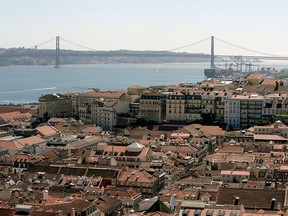The rooftops of city apartments sit beside the Tagus river near the 25th April Tagus Bridge in Lisbon, Portgual.