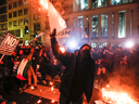 Protesters burn signs outside of the DeploraBall at the National Press Building, on Jan. 19, 2017 in Washington
