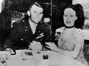 American aspiring actress and murder victim Elizabeth Short (1924 - 1947), known as the 'Black Dahlia,' sits arm-in-arm at a restaurant or bar table with American Amy Major Matthew M. Gordon Jr (? - 1945), mid 1940s. It is not proven as to whether the couple were engaged although Short claimed that they were.