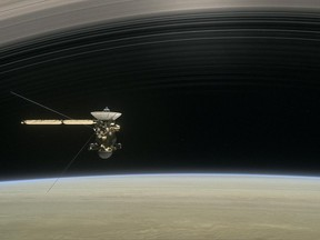 """This image made available by NASA in April 2017 shows a still from the short film """"Cassini's Grand Finale,"""" with the spacecraft diving between Saturn and the planet's innermost ring."""