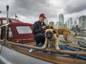 Shawn Wilson, along with his dogs Sage and her 1 month old puppy Kuma, live on his boat in False Creek in Vancouver, B.C., May 1, 2017
