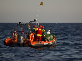 Aid workers from Proactiva Open Arms NGO recover a dead body floating on the Mediterranean sea, at 20 miles north of Zuwarah, Libya, on Wednesday, June 21, 2017