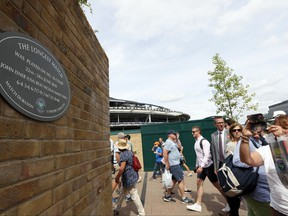 In this photo taken on Tuesday, July 4, 2017, people photograph a plaque at the Wimbledon Tennis Championships in London. And the All England Club insists there is a very simple explanation for why the marker posted on a brick wall outside Court 18 - noting it was the site of John Isner's record-breaking 70-68 fifth-set victory over Nicolas Mahut in 2010 - was missing for a bit. (AP Photo/Kirsty Wigglesworth)