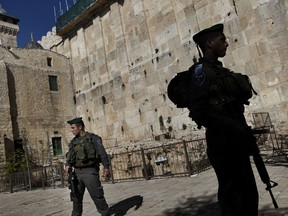 File - In this Monday, Jan. 14, 2013 file photo, Israeli border police stand guard on the site known to Jews as the Tomb of the Patriarchs, and to Muslims as the Ibrahimi Mosque, in the West Bank city of Hebron. The UNESCO World Heritage committee on Friday, July 7, 2017 put the West Bank city of Hebron on its list of world heritage in danger, a contentious decision that has drawn outrage from Israel. (AP Photo/Bernat Armangue, File)