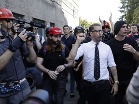 """Gavin McInnes is surrounded by supporters after speaking at a rally Thursday, April 27, 2017, in Berkeley, Calif. McInnes, co-founder of Vice Media and founder of the pro-Trump """"Proud Boys,"""" spoke at a park gathering later in the day. Until earlier this week, it would have been a safe to assume few Canadians had heard of the Proud Boys. That changed on Canada Day, when five young men in matching black polo shirts disrupted an Aboriginal ceremony in Halifax. THE CANADIAN PRESS/AP-Marcio Jose Sanchez"""