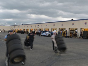Race teams rush to get cars and equipment put away ahead of an incoming thunderstorm, at Kentucky Speedway on Friday, July 7, 2017, in Sparta, Ky. The Xfinity race scheduled for Friday night was pushed back to Saturday. (AP Photo/Timothy D. Easley)