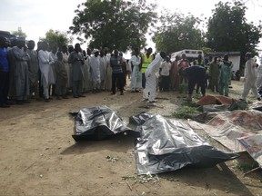 People mourn over the bodies of suicide bomb attack victims in a village near Maiduguri, Nigeria, Wednesday, July 12, 2017. Four Boko Haram suicide bombers killed over a dozen people in a series of attacks that targeted a civilian self-defense force and the people who gathered to mourn their deaths, police in Nigeria said Wednesday. It was the deadliest attack in months in the northeastern city of Maiduguri, the birthplace of Boko Haram's eight-year insurgency. (AP Photo/Jossy Ola)