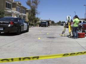 Investigators check a crime scene where two police officers and a burglar were shot on Monday, July 31, 2017, at an apartment complex in Los Banos, Calif. Authorities say the two police officers and a burglary suspect were shot in a struggle that erupted when the officers responded to a break-in report at the apartment. (AP Photo/Scott Smith)