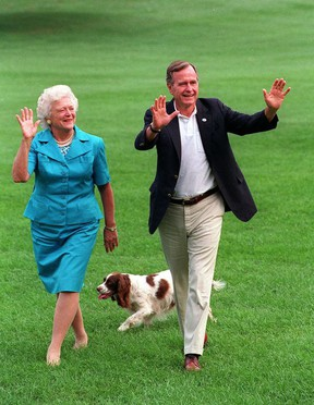 FILE- This Aug. 24, 1992 file photo shows President Bush, right, and first lady Barbara Bush walking with their dog Millie across the South Lawn as they return to the White House. (AP Photo/Scott Applewhite, File)
