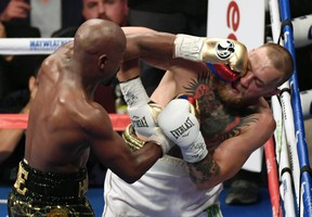 Floyd Mayweather slugs Conor McGregor in the face on Aug. 26.