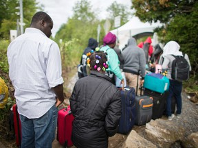 A long line of asylum seekers wait to illegally cross the Canada/US border near Champlain, New York.